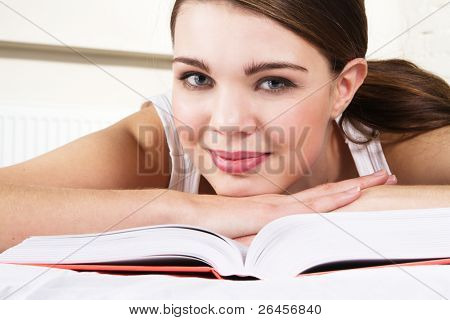 Young beautiful woman reading a book in bed