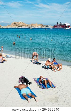 ILE-ROUSSE, FRANCE - SEPTEMBER 22, 2018: People sunbathing on the beach in Ile-Rousse, Corsica, France, and the Ile de la Pietra island and a ship at the ferry port in the background