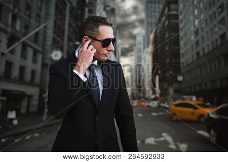 Male bodyguard, city street on background