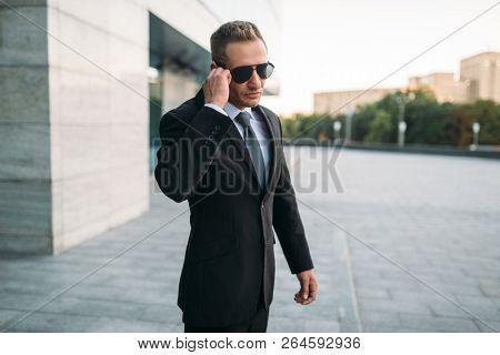 Male bodyguard talking by security earpiece