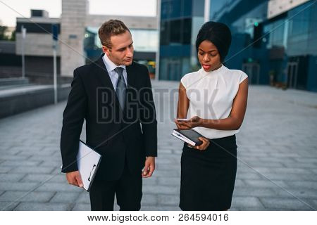 Business woman with phone, businessman with laptop