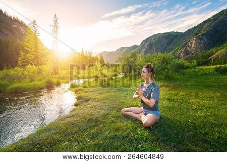 A Girl Is Meditating On A Meadow. A Tourist Is In A Lotus Pose By A Mountain River In The Rays Of Su