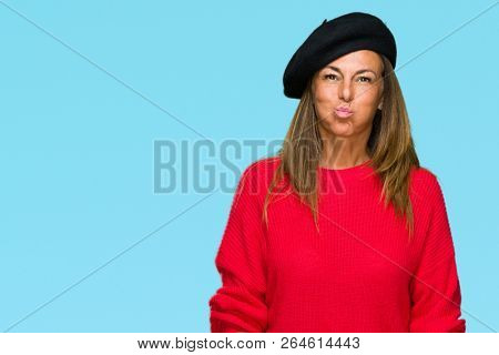 Middle age adult woman wearing fashion beret over isolated background puffing cheeks with funny face. Mouth inflated with air, crazy expression.