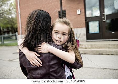 A Girl Child And His Mother Hugging Outside At School