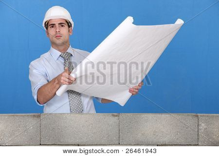 Engineer unrolling a technical drawing