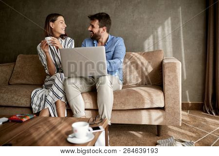Beautiful couple spending time at home, sitting on bed with laptop.