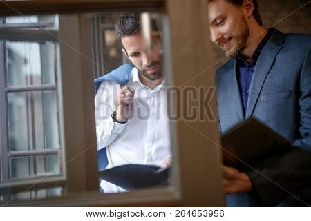 Two male businessperson together consider business plan indoor