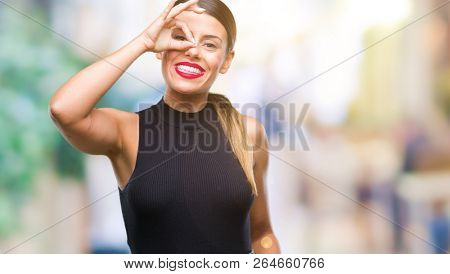 Young beautiful elegant business woman over isolated background doing ok gesture with hand smiling, eye looking through fingers with happy face.