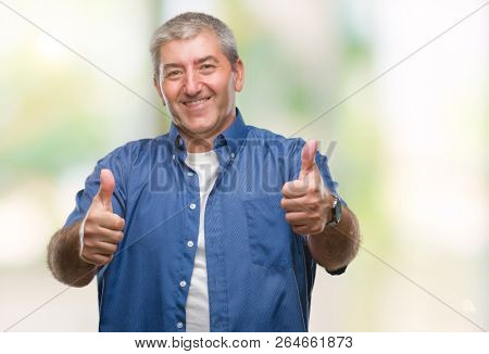 Handsome senior man over isolated background approving doing positive gesture with hand, thumbs up smiling and happy for success. Looking at the camera, winner gesture.