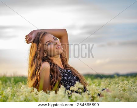 Woman posing in a field of white lavendar flowers. Portrait of Young adult girl sitting outdoors in a field of white flowers.