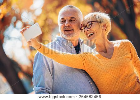Active Seniors Taking Selfies Of Them Having Fun Outside In The Autumn Forest