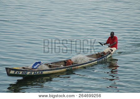 Donkorkrom, Ghana: July 20th 2016 - Man Paddling Traditional Canoe Over Lake Volta, Ghana