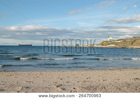 Banff Beach With The Town Of Macduff And Distinctive Church Visible Across The Bay, Aberdeenshire.