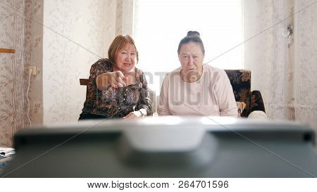 Two Elderly Women Pointint At The Tv