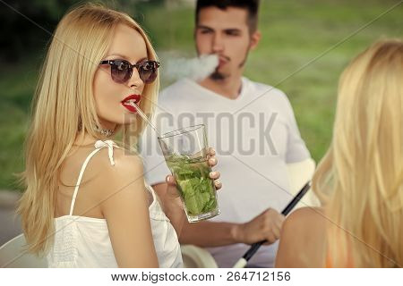 Friends At Shisha Cafe Lounge. Woman Drink Mojito Cocktail With Man. Man Vaping Hookah Pipe With Gir