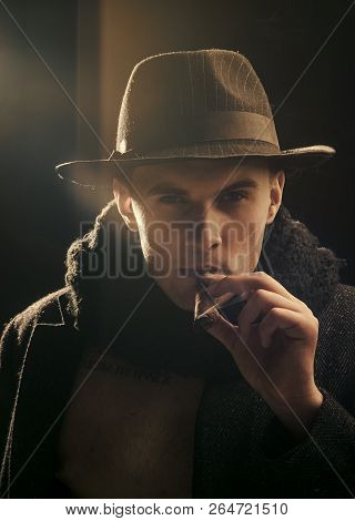Vintage Detective Concept. Man In Coat, Hat Smoking Cigar, Dark Background. Macho On Mysterious Face
