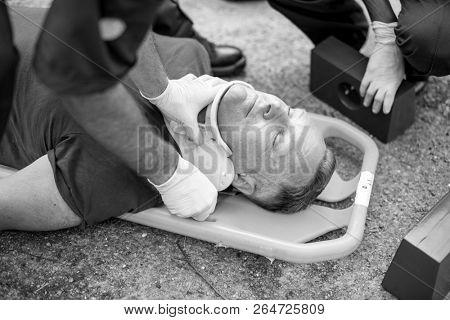 Paramedic team  placing a cervical collar to an injured man poster