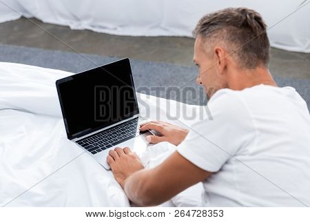 Rear View Of Man Laying In Bed And Using Laptop With Blank Screen At Home