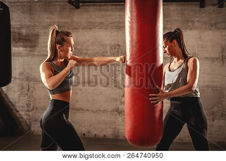 Young Muscular Woman Punching A Boxing Bag On Training With A Female Personal Trainer At The Gym.