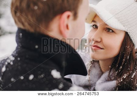 Stylish Couple In Love Embracing In Winter Snowy Mountains. Portraits Of Happy Romantic Man And Woma
