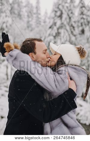 Stylish Couple Kissing In Winter Snowy Mountains. Happy Romantic Man And Woman In Luxury Clothes Gen