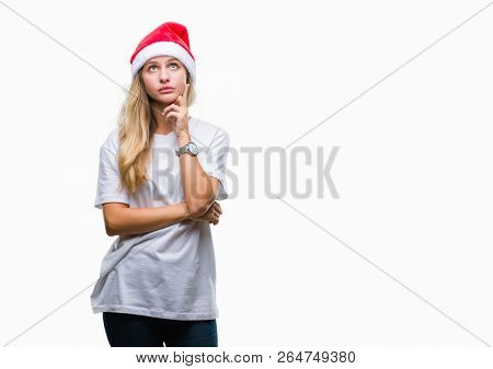 Young beautiful blonde woman wearing christmas hat over isolated background with hand on chin thinking about question, pensive expression. Smiling with thoughtful face. Doubt concept.