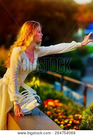 Fashion woman in autumn spring dress on city street. Female style of feminine fashionable girl model with long gold wave hair and handbag on bench outdoor. Color tone on shiny sunlight background.