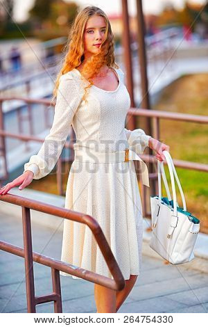 Fashion woman in autumn spring dress on city street. Female style of feminine fashionable girl model wallking fall pavement outdoor. Color tone on shiny sunlight background.