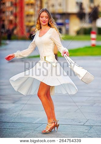 Fashion woman in autumn spring dress on city street. Female style of feminine fashionable girl model with long wave hair spinning flared skirt outdoor. Building and cobblestone pavement.