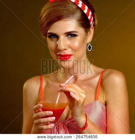Kiss blow of pin up girl drink bloody Mary cocktail. Pin-up retro female style. Girl pin-up style wearing red dress. Women prefer luxury and glamor.
