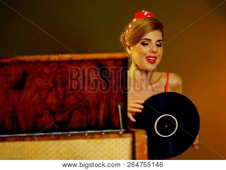 Dj retro woman vintage vinyl record turntable music and gramophone. Pin-up retro female style portrait. Girl pin-up style wearing red dress. Retro style is one of most relevant.