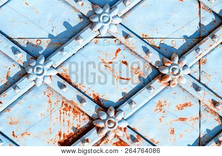 Metal architecture vintage background. Vintage metal blue grunge surface with rusty architectural metal details in form of flowers