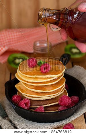 Pancakes Hotcakes With Fresh Berries And Fruit, A Man Pouring Maple Syrup On Stack