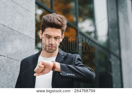 Handsome Businessman Or Student Looks At Watch. Young Man In Hurry Late For Work. Male Model On Offi