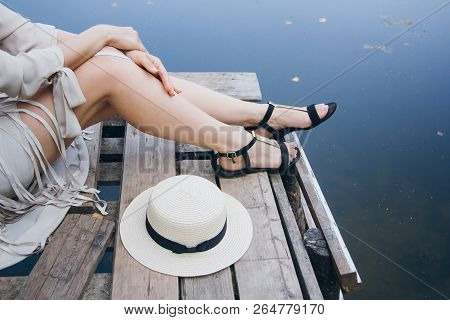 Girl In A Hat Resting On The Autumn Lake On The Bridge