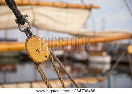 Pulley For Sails And Ropes Made From Wood On An Old Sail Boat, With Sail And Other Boats Out Of Focu