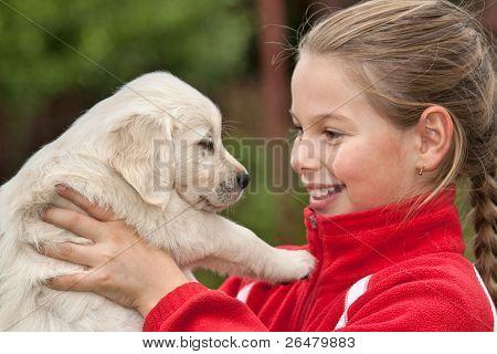 kleines Mädchen mit einem golden Retriever puppy