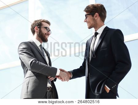 handshake business partners in a bright office