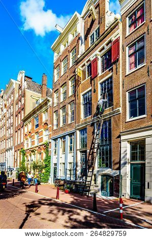 Amsterdam, The Netherlands - Sept 28, 2018: A Window Washer On A Tall Ladder Cleaning The Windows Of