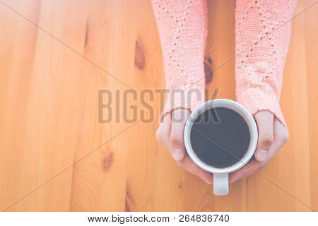 Woman Hand In Warm Pink Sweater Holding A Cup Of Coffee And Heart-shaped Handmade On A Wooden Table