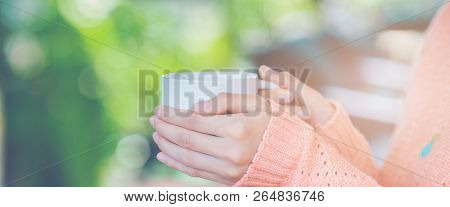 Woman Hand In Warm Sweater Holding A Cup Of Coffee.web Banner.