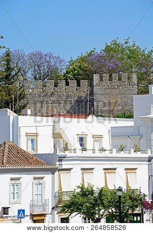 Tavira, Portugal - June 12, 2017 - Elevated View Of Town Buildings With The Castle Battlements To Th