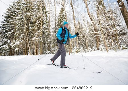 Aged active sportsman skiing down ski track in winter forest on frosty day or weekend