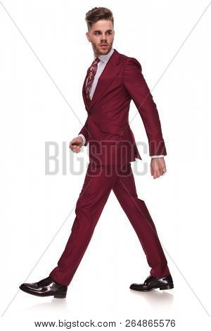 side view of confident businessman in grena suit walking on white background and looking behind, full body picture