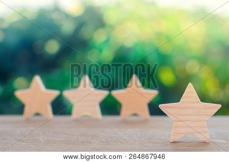 Four Wooden Stars. The Concept Of Rating And Evaluation. The Rating Of The Hotel, Restaurant, Mobile