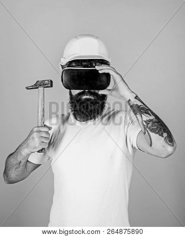 Hipster On Serious Face Wear Helmet, Hold Hammer In Virtual Reality. Man With Beard In Vr Glasses Ho