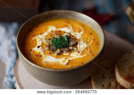 Vegetarian Pumpkin Cream Soup. Autumnal Pumpkin Soup. Home Made Pumpkin Cream Soup Decorated With Cr