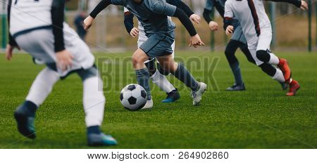 Boys Juniors In Action Play Football Soccer Match. Running Football Soccer Players. Kids At Soccer F