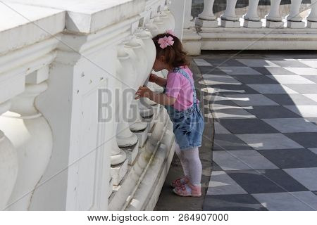 Little Girl Walks In The Park And Looks Through The Biton Fence