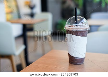 Lce Cocoa Or Coffee In Plastic Glass With Tissue On Wooden Table For Relax & Background Or Texture -
